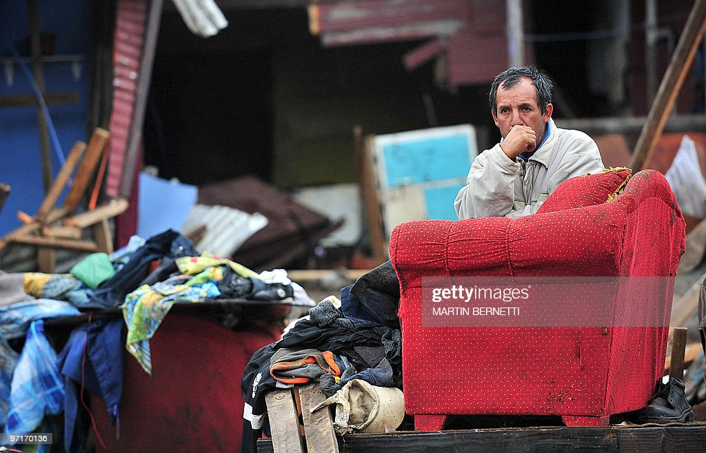A man sits among his belongings piled on the street after a tsunami hit Penco 10 kms from Concepcion the day after a huge 88magnitude earthquake...