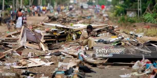 A man sits amongst the debris strewn around him after the massive tsunami wave swept across coastal Sri Lanka December 28 2004 in Colombo Sri Lanka...