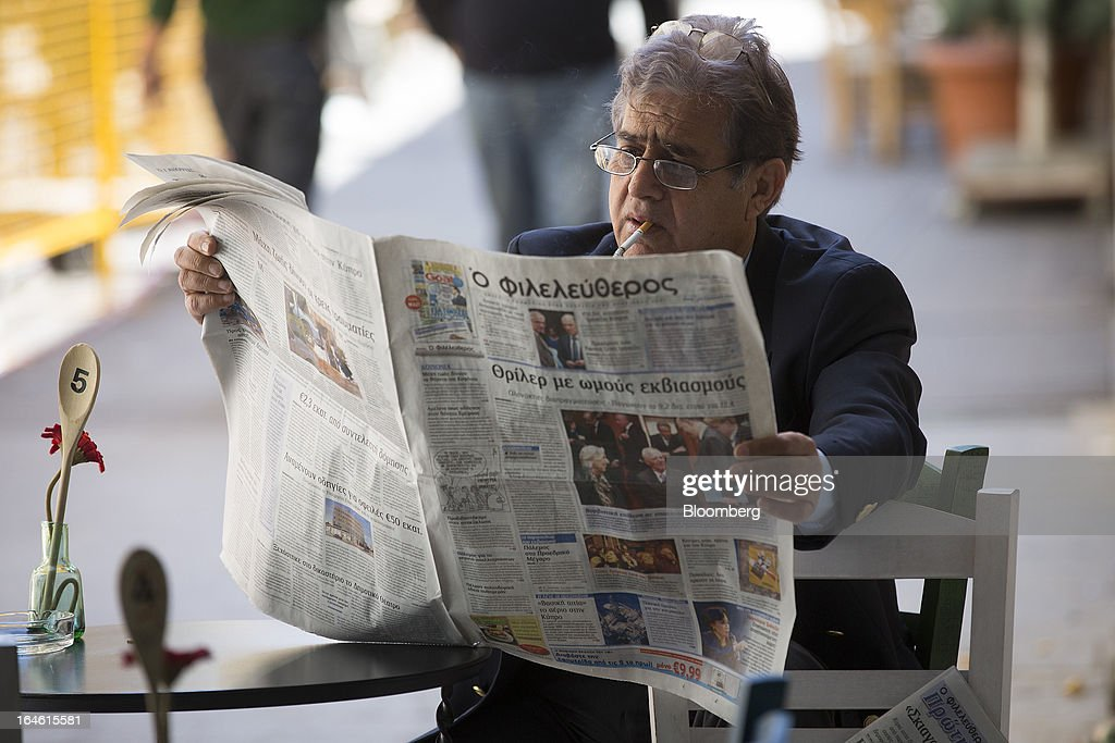 A man sits and smokes a cigarette while reading a newspaper at a cafe in Nicosia, Cyprus, on Monday, March 25, 2013. In a replay of tensions over aid for Greece at the outset of the crisis, European governments had wrangled over aid for Cyprus for nine months, exposing holes in the revamped economic management system that was built in three years of emergency policymaking, often at all-night summits. Photographer: Photographer: Simon Dawson/Bloomberg via Getty Images