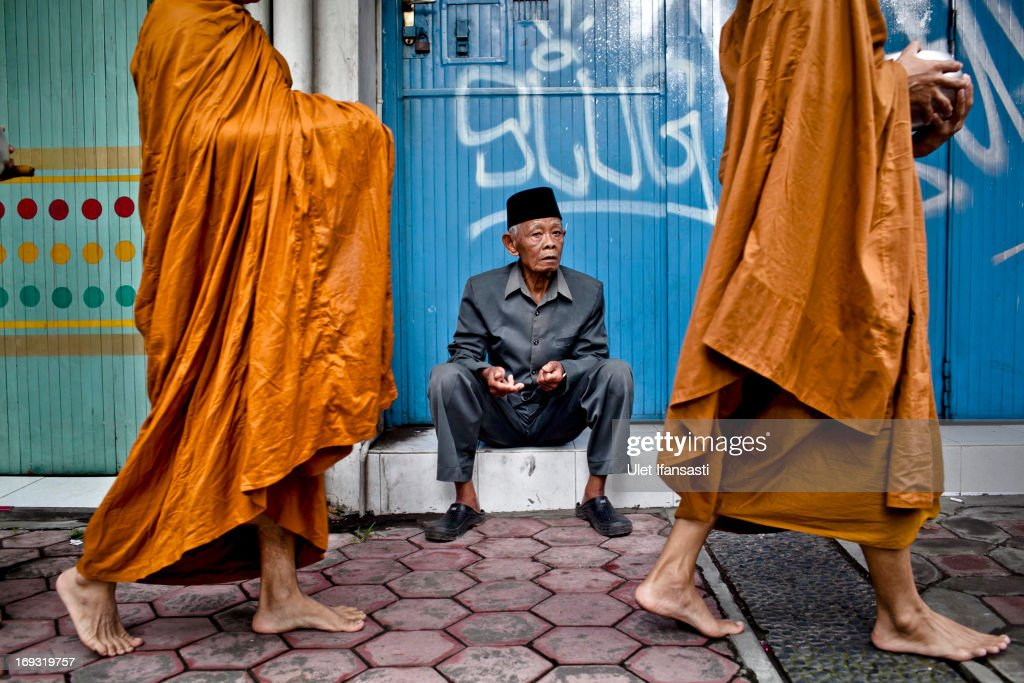 A man sits as Buddhist monks walk around the streets to receive religious alms from Buddhist members during Pindapata procession on May 23, 2013 in Magelang, Central Java, Indonesia. As many as 100 monks took to the streets of Magelang city in a procession known as Pindapata, ahead of Vesak day which celebrates the birth of the Lord Buddha.