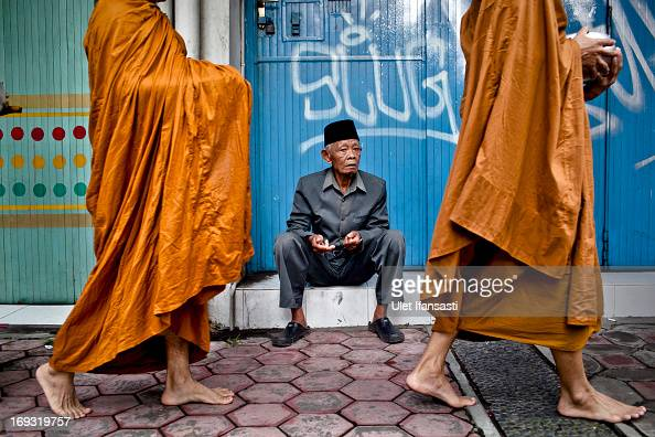 A man sits as Buddhist monks walk around the streets to receive religious alms from Buddhist members during Pindapata procession on May 23 2013 in...