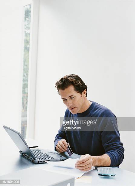 Man Sits at a Desk With His Laptop, Paying a Bill Online With His Credit Card
