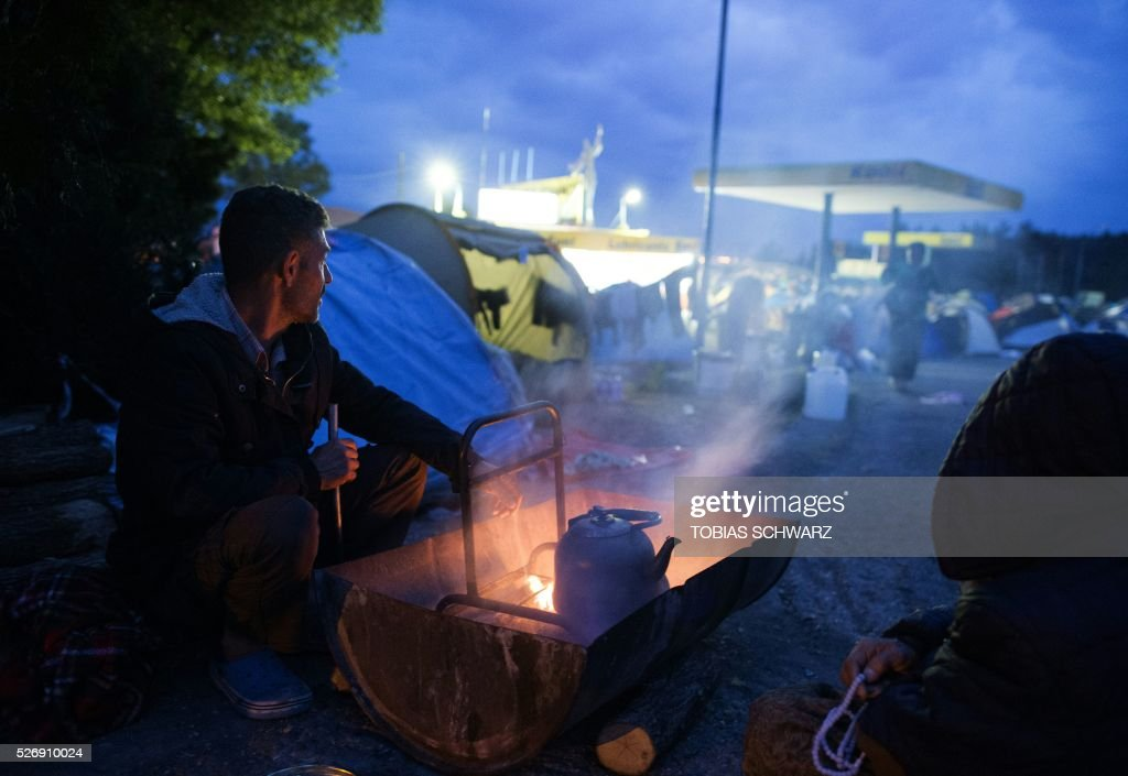 A man sits at a fire next to a gas station at a makeshift camp for migrants and refugees near the village of Idomeni not far from the Greek-Macedonian border on May 1, 2016. Some 54,000 people, many of them fleeing the war in Syria, have been stranded on Greek territory since the closure of the migrant route through the Balkans in February. / AFP / TOBIAS