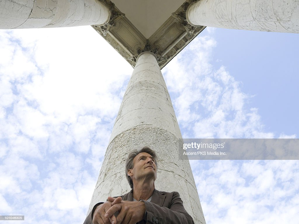 Man sits at base of marble pillars, looks awy : Stock Photo