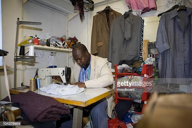 Man sits at machine in textiles workshop