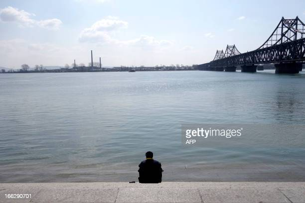 A man sits at the bank of Yalu River in the Chinese border city of Dandong in China's northeastern Liaoning province on April 11 2013The biggest...
