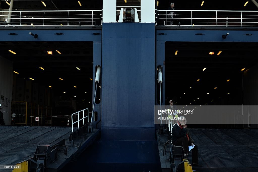 A man sits at the ramp of a docked ferry at the port of Piraeus, near Athens, during a 48-hours strike on 31 January, 2013. Sailors kicked off a two-day walkout, buses and trains were at a standstill and civil servants planned to hold a three-hour work stoppage against the government's cutbacks. AFP PHOTO / ARIS MESSINIS