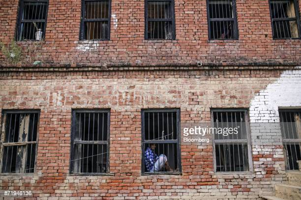 A man sits at the window of a silk saree workshop in Varanasi Uttar Pradesh India on Friday Oct 27 2017 In Varanasi where the manufacture of 45meter...