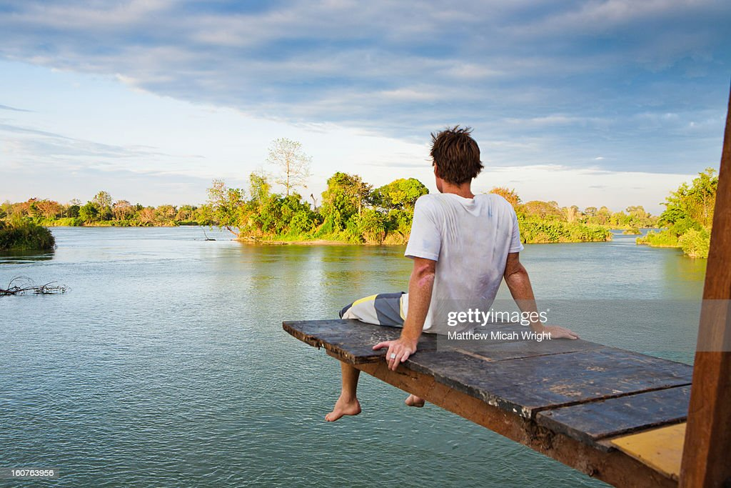 A man sits atop a high diving plank : Stock Photo