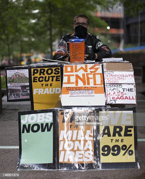 A man sits behind a table offering literature for the Occupy Wall Street movement in Zuccotti Park June 5 2012 in New York City