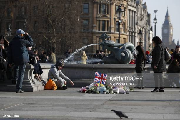 A man sits beside a small memorial and floral tributes to the victims of the March 22 terror attack on the British Parliament and Westminster Bridge...