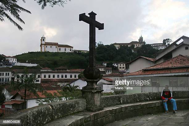 A man sits by a cross during traditional Semana Santa festivities on Good Friday on April 3 2015 in Ouro Preto Brazil Holy Week marks Easter...