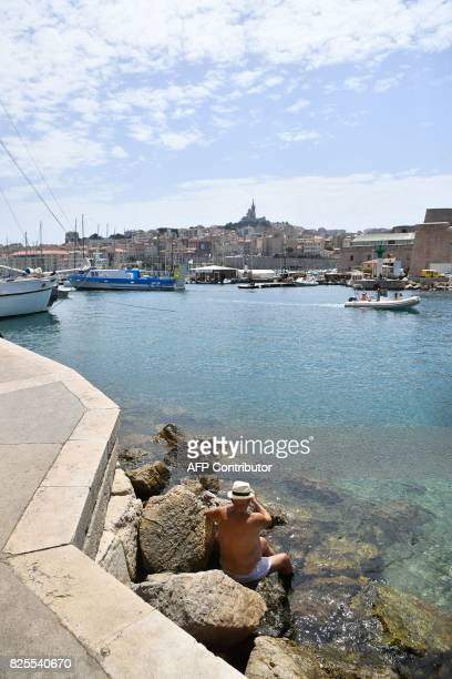 A man sits by the sea near the Vieux Port in Marseille southern France on August 2 2017 as a heatwave hit the city / AFP PHOTO / BERTRAND LANGLOIS