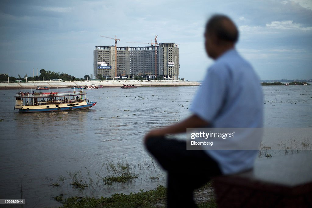 A man sits by the Tonle Sap river as a development by Sokha Hotels & Resorts, a unit of Sokimex Group, stands under construction in Phnom Penh, Cambodia, on Saturday, Nov. 17, 2012. U.S. President Barack Obama arrives in Phnom Penh later today to join the Association of Southeast Asian Nations (Asean) East Asia Summit, which also includes leaders from Japan, South Korea, India, Russia, Australia and New Zealand. Photographer: Will Baxter/Bloomberg via Getty Images