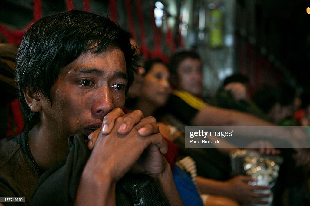 A man sits crying on a packed C130 aircraft as emotions take over after he and hundreds of other victims of super Typhoon Haiyan are evacuated from the area on November 12, 2013 in Tacloban, Philippines. Four days after the typhoon devastated the region many have nothing left, they are without food or power and most lost their homes. Around 10,000 people are feared dead in the strongest typhoon to hit the Philippines this year.