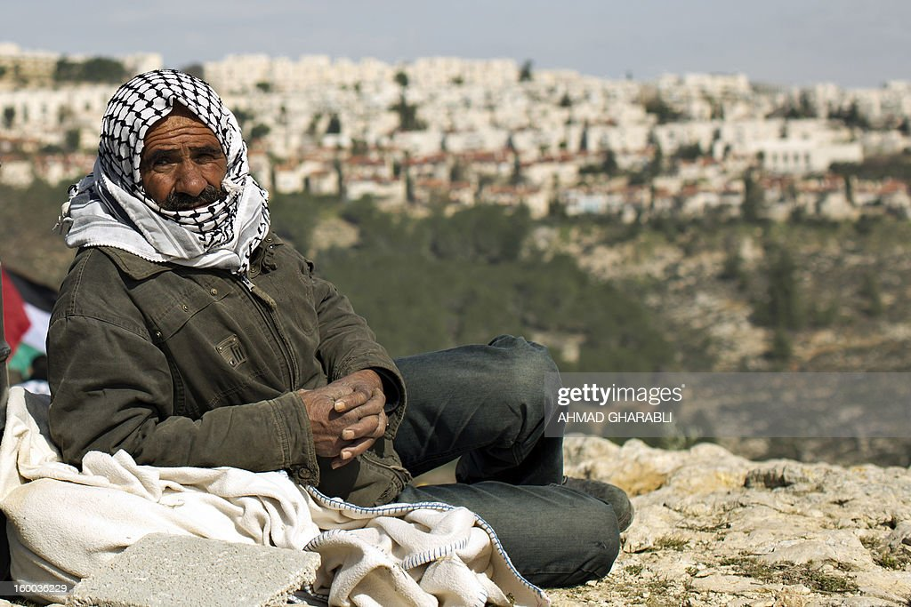 A man sits during a protest of Palestinian activists over confiscated lands by Israeli army on January 25, 2013 in the West Bank village of Beit Iksa. Activists said recently that the Israeli army would confiscate over 500 dunams (124 acres, 50 hectares) of land by the village, located on the northwestern outskirts of Jerusalem. AFP PHOTO/AHMAD GHARABLI