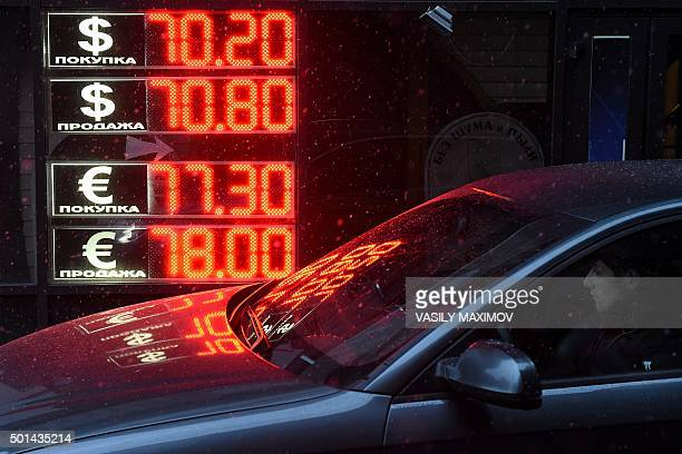A man sits in a car parked next to a board listing foreign currency rates against the Russian ruble in central Moscow on December 15 2015 Russia's...