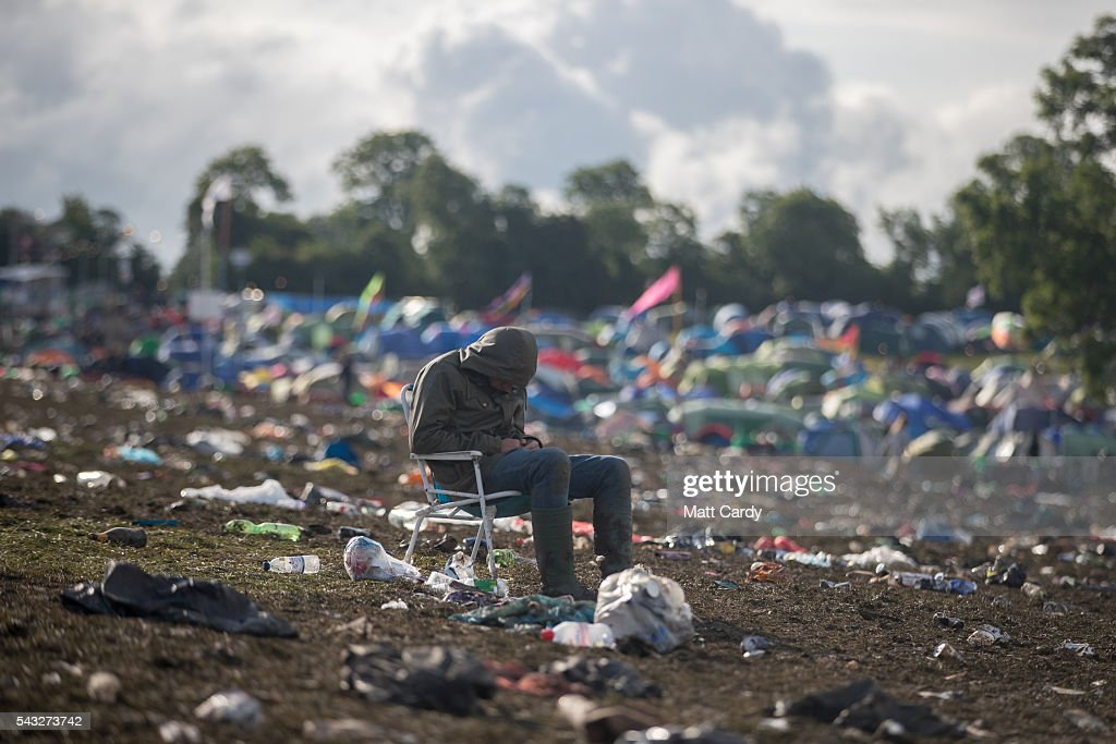 A man sits in a chair left behind as the clear up begins at the Glastonbury Festival 2016 at Worthy Farm, Pilton on June 26, 2016 near Glastonbury, England. The Festival, which Michael Eavis started in 1970 when several hundred hippies paid just £1, now attracts more than 175,000 people.