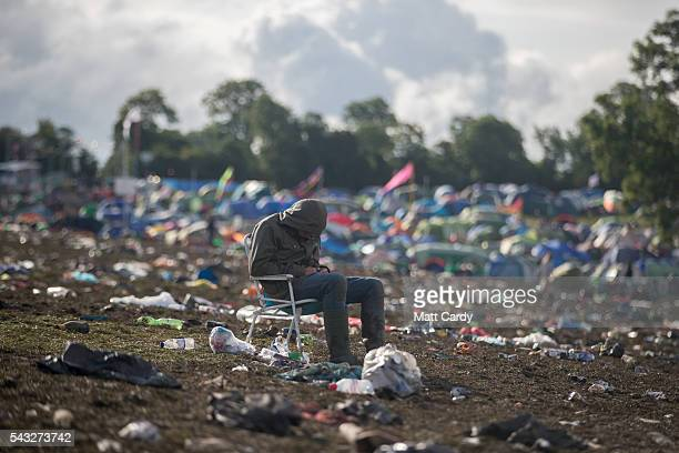 A man sits in a chair left behind as the clear up begins at the Glastonbury Festival 2016 at Worthy Farm Pilton on June 26 2016 near Glastonbury...