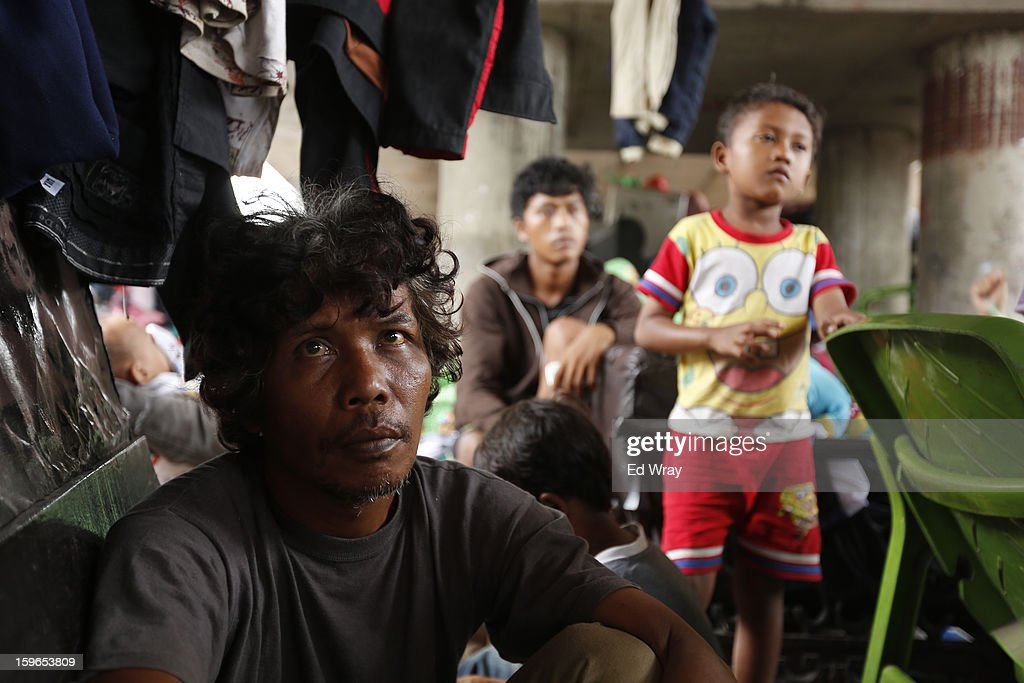 A man sits in a makeshift refugee camp for flood victims under a highway flyover on January 18, 2013 in Jakarta, Indonesia. According to the National Disaster Management Agency, about 50 percent of the capital is under water following the floods which have so far claimed eleven lives and displaced thousands of Indonesians.