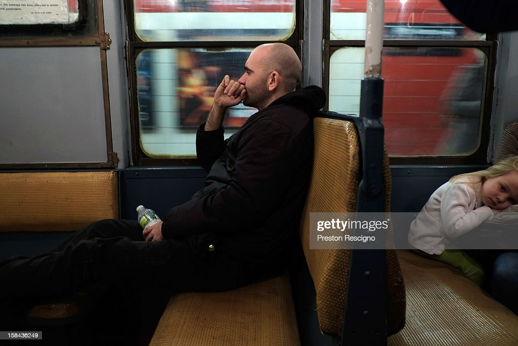 A man sits in a vintage New York City subway car as it pulls into a station on December 16, 2012 in New York City. The New York Metropolitan Transportation Authority (MTA) runs vintage subway trains from the 1930's-1970's each Sunday along the M train route from Manhattan to Queens through the first of the year.