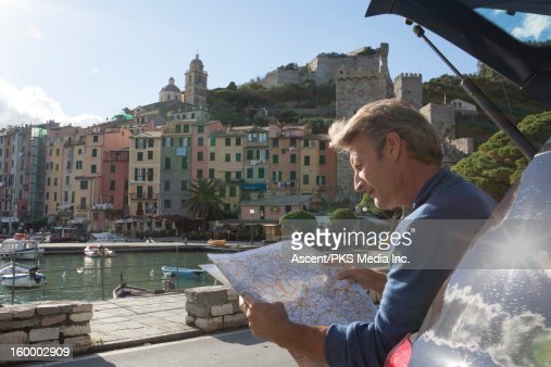 Man sits in back of car, consults map, Portovenere : Stock Photo