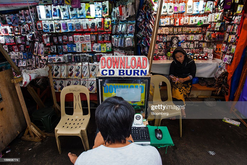 A man sits in front of a computer at a stall selling electronics and mobile phone accessories at the Divisoria market in Manila, the Philippines, on Tuesday, Jan. 22, 2013. Philippine government bonds advanced on speculation the central bank will hold its benchmark interest rate at a record low at a meeting tomorrow, supporting demand for the nation's debt. Photographer: Julian Abram Wainwright/Bloomberg via Getty Images