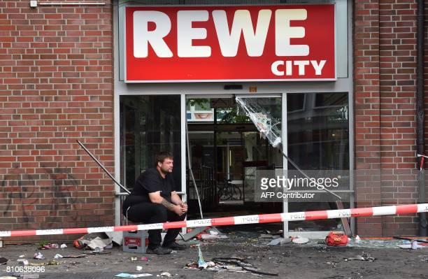A man sits in front of a destroyed Rewe City supermarket after riots in Hamburg's Schanzenviertel district on July 8 2017 in Hamburg northern Germany...