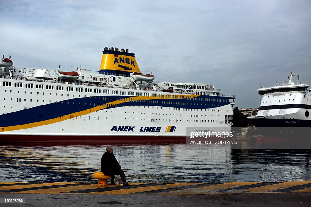 A man sits in front of a docked ferry at the port of Piraeus, near Athens, during a 48-hours strike on February 2, 2013. Sailors kicked off a two-day walkout, buses and trains were at a standstill and civil servants planned to hold a three-hour work stoppage against the government's cutbacks. AFP PHOTO / ANGELOS TZORTZINIS