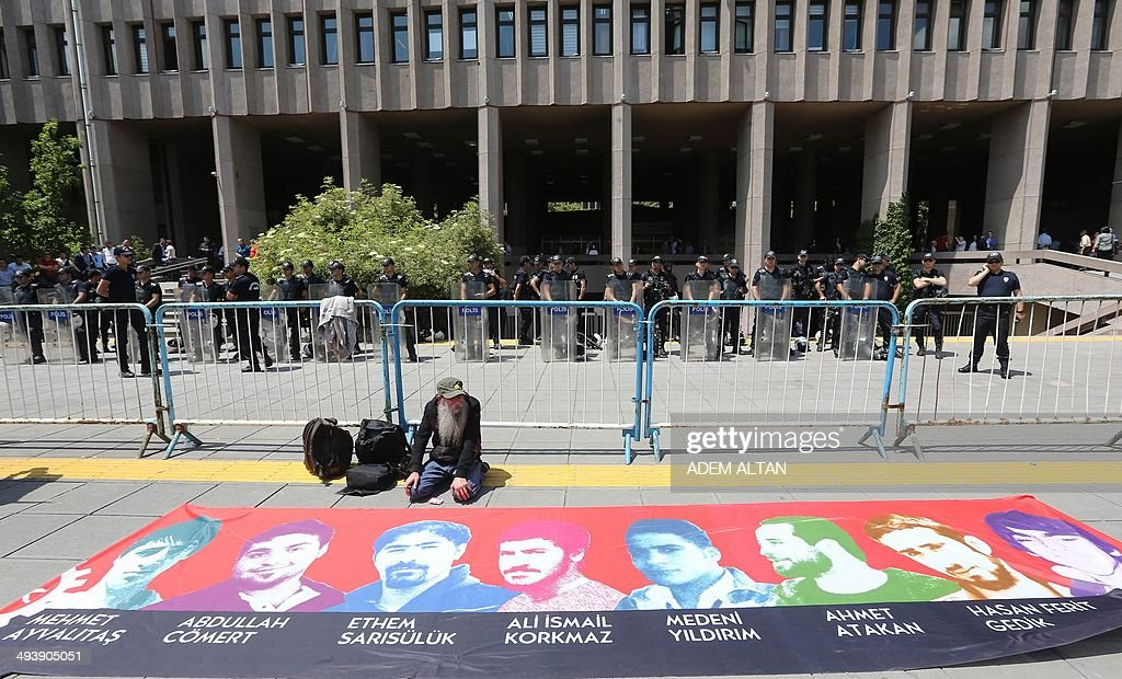 A man sits in front of a giant poster with printed pictures of victims of the spring 2013 Gerzi protests as police officers stand guard outside a courthouse during the trial of a police officer accused of killing Ethem Sarisuluk, a 26-year-old Turkish man, in anti-government protest in June, in Ankara, May 26, 2014.