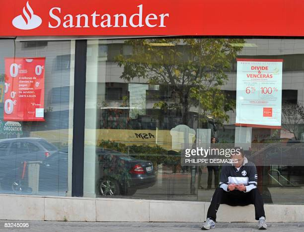 A man sits in front of a Santander bank in Madrid on October 13 2008 Santander the biggest Spanish bank said it had injected one billion pounds into...