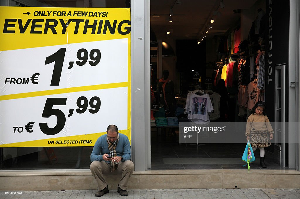 A man sits in front of a shop poster offering discounts one day before the second run-off of the Cypriot presidential elections in Nicosia, on February 23, 2013. A second-round on February 24, being closely watched in European capitals pits right-wing opposition leader Nicos Anastasiades against Stavros Malas, who is backed by the communist party in power during the economic downturn, Akel. AFP PHOTO / YIANNIS KOURTOGLOU