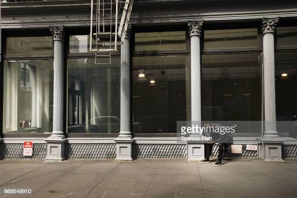 A man sits in front of an empty retail space in lower Manhattan on April 17 2017 in New York City As American's shopping habits continue to migrate...