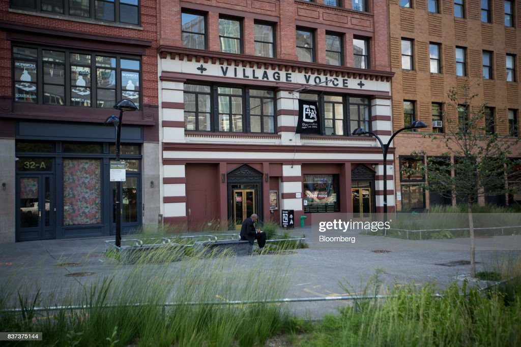A man sits in front of the former headquarters for The Village Voice in the East Village neighborhood of New York, U.S., on Tuesday, Aug. 22, 2017. Peter Barbey, owner of The Village Voice since 2015, has decided to no longer produce a print edition of the alt-weekly publication. The company's announcement, made Tuesday afternoon, came as a surprise, a shock and a disappointment to the larger media industry on Twitter. Photographer: Michael Nagle/Bloomberg via Getty Images