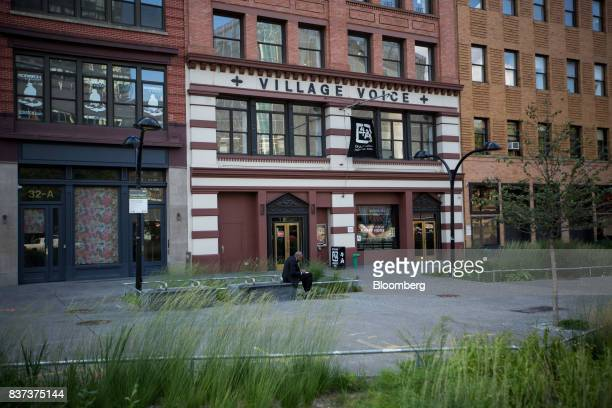 A man sits in front of the former headquarters for The Village Voice in the East Village neighborhood of New York US on Tuesday Aug 22 2017 Peter...