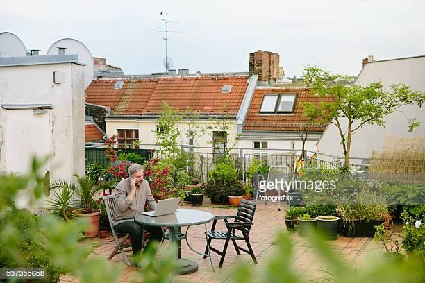 Mann sitzt in seinem Garten auf der Dachterrasse und arbeitet auf laptop