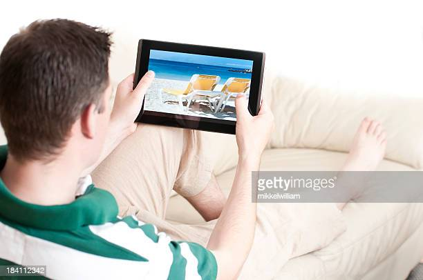 Homem sentado no sofá com tablet computador