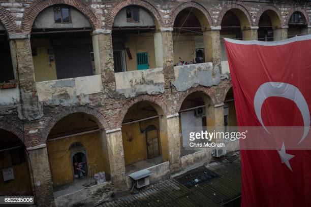 A man sits in the entrance of a workshop in the Buyuk Yeni Han on May 10 2017 in Istanbul Turkey The hans of Istanbul are courtyard areas off the...