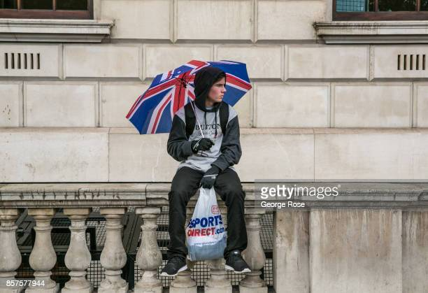 A man sits in the rain near Westminster Underground Station with a Union Jack umbrella on September 13 in London England Great Britain's move toward...