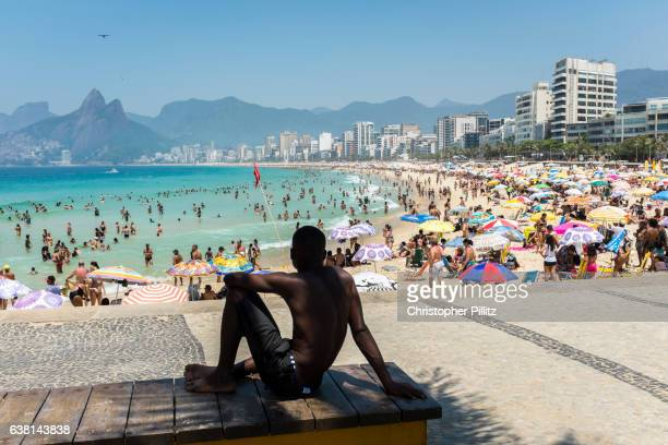 Man sits in the shade of a palm tree surveying life on a packed Ipanema beach.