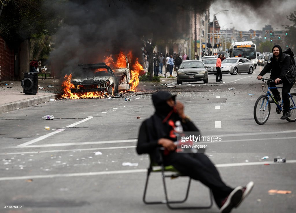 A man sits in the street near burning cars near the intersection of Pennsylvania Avenue and North Avenue April 27 2015 in Baltimore Maryland Riots...