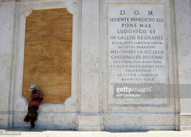 A man sits in the the shade of Piazza di Spagna on July 15 2017 in central Rome / AFP PHOTO / ANDREAS SOLARO