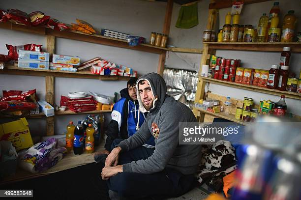 A man sits inside a shop in the camp known as the 'New Jungle' on December 2 2015 in Calais France Thousands of migrants continue to live in the...