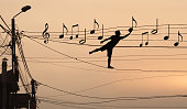 Sillouthe of a man putting music notes on wires . Concept of a crazy composer