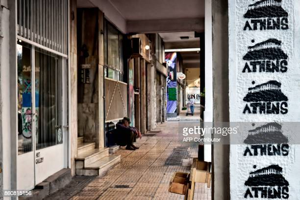 A man sits near artwirks by Greek graffiti artist Cacao Rocks in central Athens on October 11 2017 An ongoing exhibition devoted to 'Artists in...