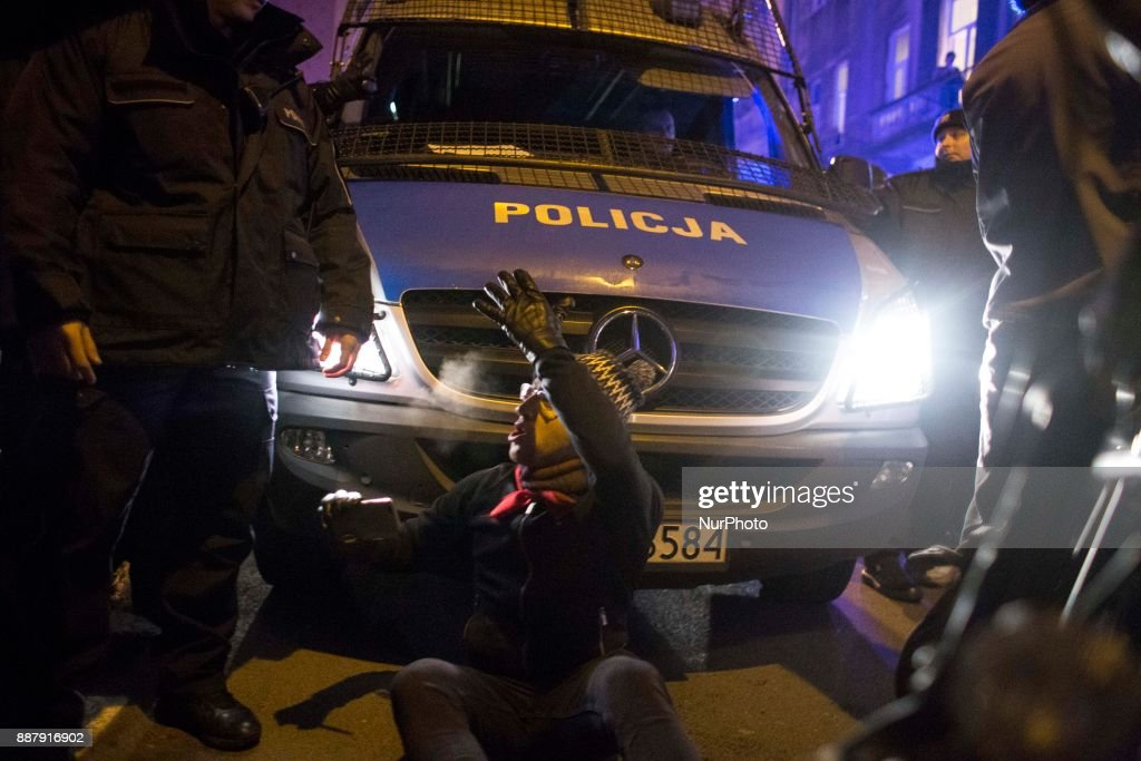 Man sits near police truck during illegal demonstration near Polish parliament organized by opposition group Obywatele RP in Warsaw on December 7, 2017.