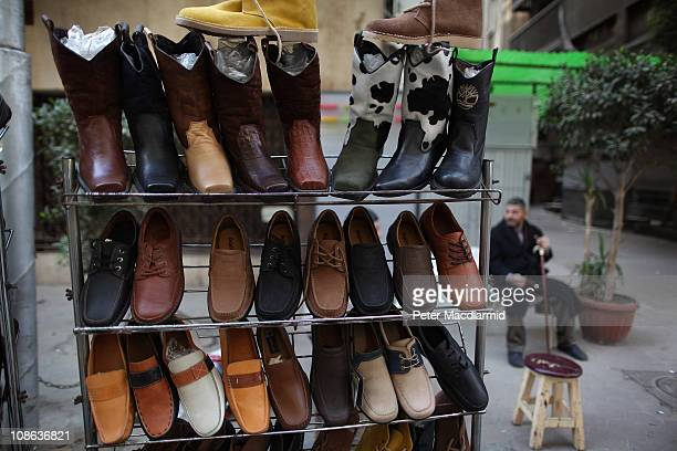 A man sits near street sellers's shoes on January 31 2011 in Cairo Egypt As President Mubarak struggles to regain control after six days of protests...
