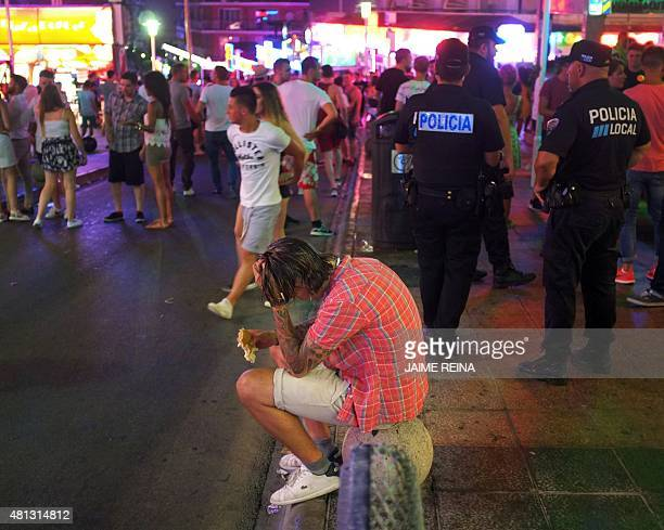 A man sits nex to local policemen in Punta Ballena street in Magaluf holiday resort in Calvia on the Spanish Mallorca Island on July 19 2014 Known...
