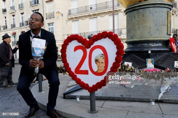 A man sits next to a heatshaped sign marking the 20th anniversary of the death of the Princess Diana at the Flame of Liberty monument which became an...