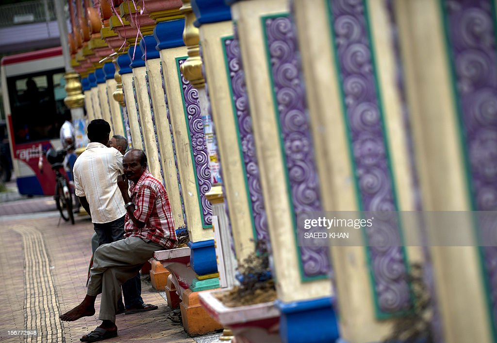 A man sits next to a row of columns in the Brickfields area, also known as Little India, in Kuala Lumpur on November 20, 2012. Malaysia's economy grew a better-than-expected 5.2 percent in the third quarter as domestic demand continued to compensate for a slowdown in exports, the government said recently. AFP PHOTO / Saeed KHAN